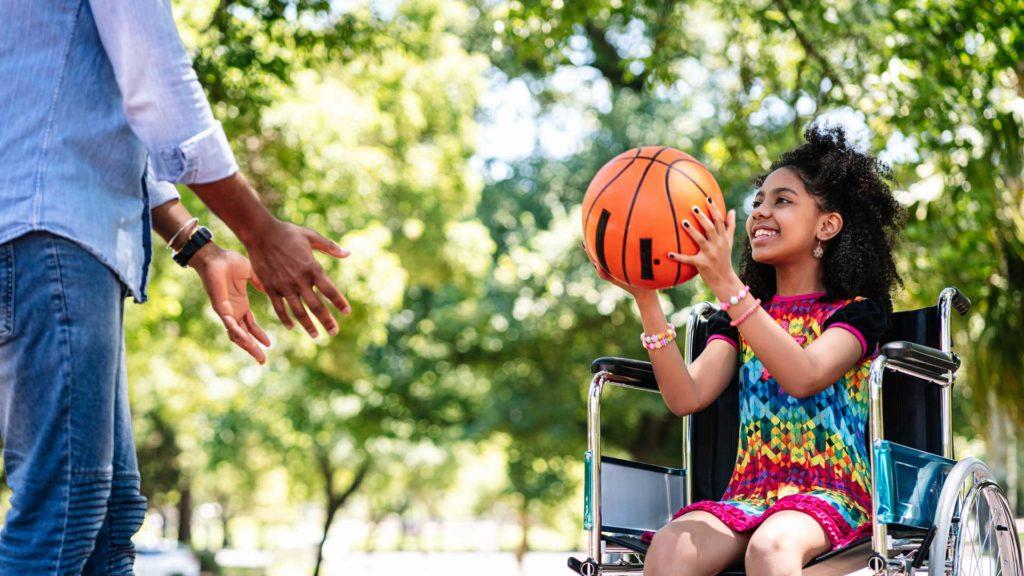girl and dad playing basketball